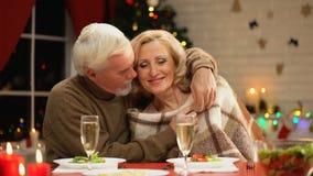 Esposa de envelhecimento da coberta do marido com manta acolhedor e aperto dela maciamente, véspera do Xmas video estoque