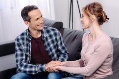 esposa e marido que guardam as mãos ao descansar no sofá fotografia de stock