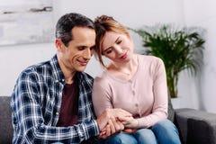 esposa e marido que guardam as mãos ao descansar no sofá imagem de stock royalty free