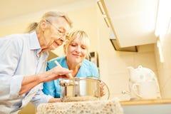 Esposa e sênior do serviço social na cozinha imagens de stock