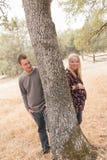Esposa embarazada con el marido al lado del árbol Foto de archivo libre de regalías