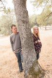 Esposa embarazada con el marido al lado del árbol Fotos de archivo