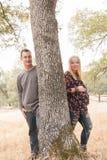 Esposa embarazada con el marido al lado del árbol Imagenes de archivo