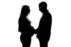 Esposa embarazada y marido de la silueta que llevan a cabo las manos Foto de archivo