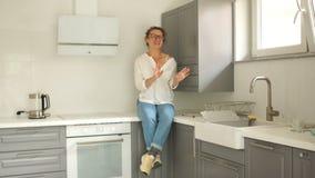 A esposa feliz exulta a compra de uma cozinha nova Bens imobiliários e reparos Dança da jovem mulher no interior de um novo filme