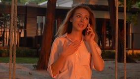 Esposa joven de la cámara lenta que sostiene el smartphone que se sienta cerca de propia mansión metrajes