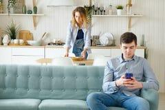 A esposa leva embora pratos que o marido se senta no sofá com telefone fotografia de stock royalty free