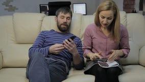 A esposa loura em um sofá lê suas notas em um caderno e em seu marido que sentam-se próximo e que conversam no telefone filme