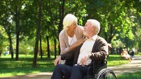 Esposa madura que toma el cuidado de su marido querido en silla de ruedas, matrimonio feliz almacen de video