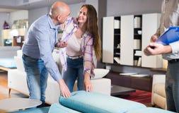 A esposa no marido está testando a mobília nova Imagens de Stock