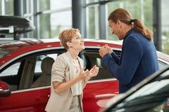 Esposa nova feliz que pede para comprar um carro novo para ela no negócio imagem de stock