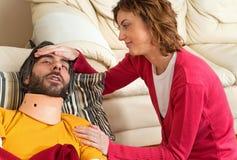 A esposa ocupa do marido ferido Foto de Stock