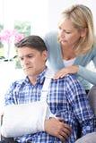 Esposa que consola o marido que sofre com ferimento do braço fotografia de stock royalty free