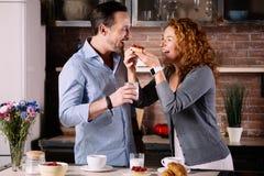 Esposa que dá o bolo ao marido imagem de stock royalty free