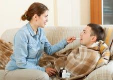 Esposa que da el jarabe de la tos a su marido Fotografía de archivo