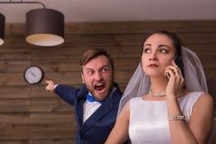 Esposa que fala pelo telefone, marido que mostra no relógio foto de stock