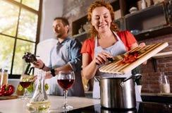 A esposa que põe ingredientes cortou no potenciômetro Fotografia de Stock Royalty Free