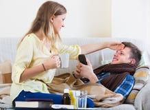 Esposa que toma el cuidado del marido con el tubo Imagen de archivo libre de regalías