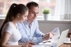 Esposa satisfecha y marido que comprueban cuentas en casa imagenes de archivo