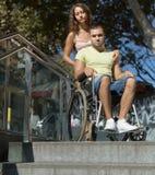 Esposa trastornada con el hombre en silla de ruedas en las escaleras Fotos de archivo libres de regalías