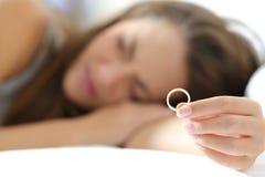 Esposa triste após o divórcio que guarda uma aliança de casamento imagens de stock royalty free