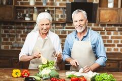 Esposa y marido que cocinan la ensalada imágenes de archivo libres de regalías
