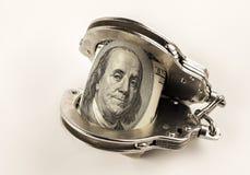 Esposas de los dólares y de la policía del acero Imágenes de archivo libres de regalías