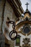 Esposas del hierro usadas para torturar esclavos delante de una iglesia imágenes de archivo libres de regalías