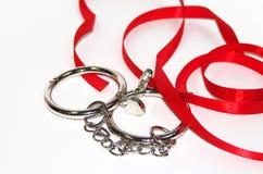 Esposas del metal aisladas en el fondo blanco y la cinta roja Foto de archivo