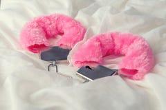 Esposas mullidas del rosa en el fondo blanco de la tela foto de archivo libre de regalías