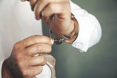 Esposas y llave de la mano del hombre fotos de archivo