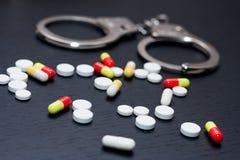 Esposas y píldoras y drogas en la tabla de madera fotografía de archivo