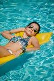Esposizione al sole della giovane donna nella piscina della località di soggiorno di stazione termale Fotografia Stock