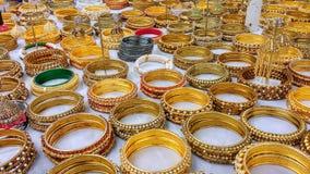 Esposizione dei braccialetti dell'oro da vendere sul panno bianco Immagini Stock Libere da Diritti