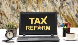 Esposizione del monitor del computer portatile dell'ufficio progetti di parola di riforme fiscali Immagine Stock