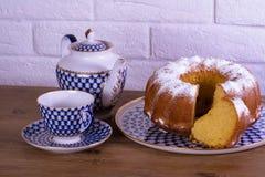 Esposizione della tazza della torta di mele di tè e bollitore sulla tavola di legno e fondo bianco del mattone, tazza da the russ Fotografie Stock Libere da Diritti