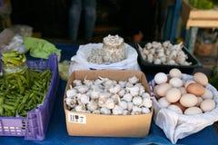 Esposizione delle cipolle, dell'aglio, delle uova, dei piselli e dei semi di zucca verdi e bianchi freschi Frutta e verdure ad un Fotografia Stock