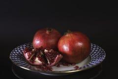 Esposizione di granato sul fondo russo d'annata del nero del piatto della porcellana, in pieno e sul mezzo granato, frutta natura Immagini Stock Libere da Diritti