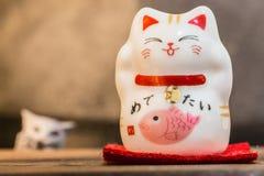 Esposizione felice del gatto della ceramica sveglia sulla tavola immagine stock