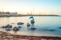 Esposizione lunga della statua del delfino nell'acqua in Sardegna -  Fotografia Stock