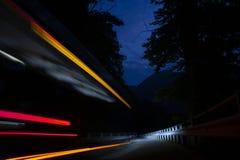 Esposizione lunga delle luci dell'automobile nella notte immagine stock
