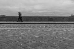 Esposizione lunga di un pedone che cammina su un ponte un giorno piovoso fotografia stock libera da diritti