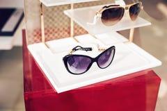 Esposizione nel negozio, stile di vita di modo degli occhiali da sole dei pantaloni a vita bassa Fotografia Stock