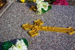 Esposizione trasversale dorata sulla pietra tombale, esposizione del fiore per il ricordo fotografia stock libera da diritti