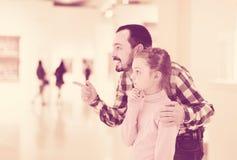 Esposizioni d'esplorazione interessate della figlia e del padre in museo immagini stock libere da diritti
