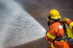 Espray de agua del bombero por la manguera de bomberos de alta presión imagenes de archivo