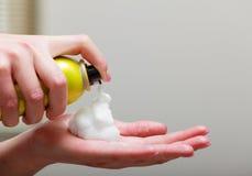 Espray de la crema batida de pelo de la mano del peluquero del primer. En salón de belleza de la peluquería Foto de archivo
