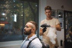Espray de rociadura de la fijación del pelo del peluquero en un cliente en un fondo borroso Concepto profesional de la peluquería Foto de archivo libre de regalías