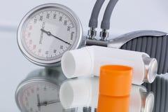 Espray del asma e indicador de la presión arterial Fotografía de archivo