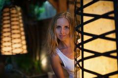 Espreitadela atrativa da menina para fora da lanterna do jardim imagens de stock royalty free